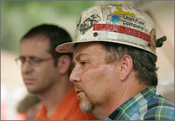 Doug Johnson, director of corporate services for Murray Energy Corp., forefront, and company vice president Rob Moore talk about the six trapped coal miners at the entrance to the Crandall Canyon Mine, northwestern of Huntington, Utah, on Monday.