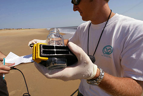 Brad DeLashmutt, 33, an environmental specialist for the Virginia Department of Health, collects water samples in Virginia Beach.