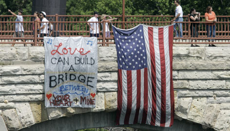 A sign and a flag are tied to the Stone Arch pedestrian bridge Monday near a public memorial in Minneapolis' Gold Medal Park for the victims of last week's I-35W bridge collapse.
