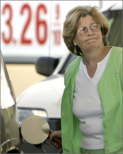 Wanda Marsh of Papillion, Neb., fills her car with gasoline in Omaha, in this July 2007 file photo. Higher gasoline taxes may help fund infrastructure repairs across the USA.