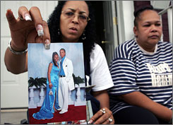 Family friend Cathy Rainey, left, holds up a 2006 photo of Iofemi Hightower, 20, and Terrance Aeriel, 18, as Shalga Hightower, right, talks about her daughter, Iofemi, who was killed along with Aeriel in an execution-style shooting in a schoolyard late Saturday night.