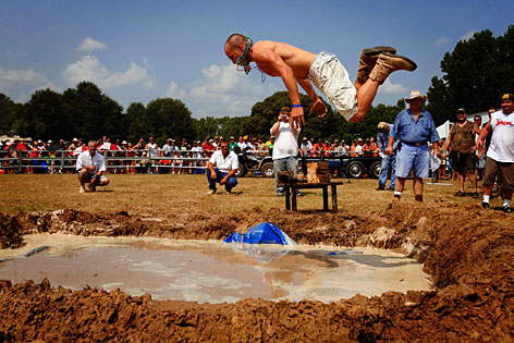 Blake Harris belly flops into the mud pit during the Texas Redneck Games at the Pool Ranch in Athens, Texas, Saturday. Patterned after the original Redneck Games, which began more than 10 years ago in Georgia, the third-annual Texas games this year attracted between 5,000 and 6,000 people.