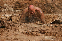 "Robert Page eats some mud after a belly buster during the Texas Redneck Games at the Pool Ranch in Athens, Texas, Saturday. The four-day ""Redneck Games"" took place about 70 miles southeast of Dallas and included large crowds, live music and various competitions."