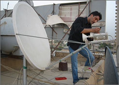 Ahmed Hassan, an installer for Sama Baghdad Company, adjusts an antenna dish in the Al Asad district of Baghdad. Hassan's boss, Sama Sa'ad, has to screen would-be customers before sending Hassan to their homes to make sure Hassan won't be kidnapped. 