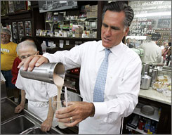 Mitt Romney pours a milkshake during a visit to the Wilton Candy Kitchen in Wilton, Iowa, Wednesday.