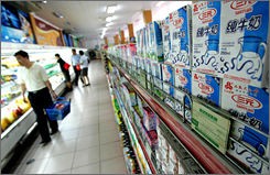 Customers walk past milk products at a supermarket in Beijing Friday. Milk is now trading at record highs.