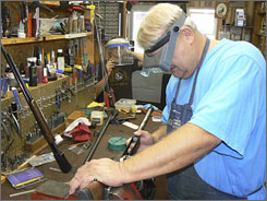 Bob Heiser of Dakota Gunworks, foreground, works on an older model pump shotgun, the kind of gun he favors because of the craftsmanship.