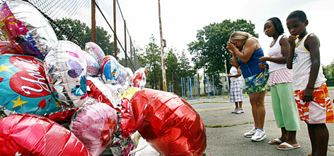 Donia Turner, third right, prays outside the makeshift memorial in the schoolyard where three friends were killed, and a fourth shot, on Aug. 4.