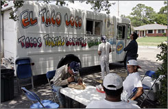 Customers line up at the El Taco Loco truck in New Orleans' Lakeview section in June. Lunch trucks serving Latin American fare cater to immigrant laborers helping rebuild the city.