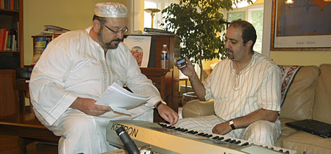 Alberto Mizrahi, left, and Kader Rhanime, listen to called Haj Youness, via cell phone in Casablanca, sing the key of the musical piece they are practicing in Chicago.