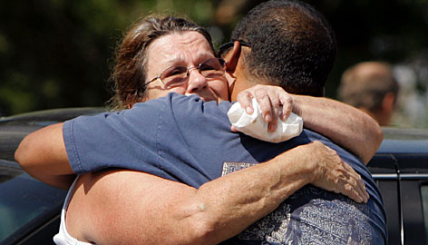 Wanda Parsons, left, hugs Kelson Rehobson, the brother of Kernal Rehobson, Monday, in Goodman, Mo. Friends and family are struggling to understand why a gunman would interrupt a church service led by Kernal Rehobson with a barrage of gunfire killing him and two people and wounding five others on Sunday in the nearby town of Neosho, Mo.