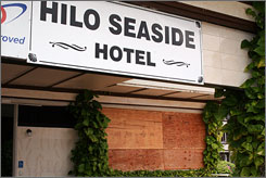 Boards cover the lobby windows of the Hilo Seaside Hotel, Monday, in Hilo, Hawaii. Another Hilo hotel, Naniloa Volcanoes Resort, reported approximately 20 guest cancellations in the last 24 hours due to weather-related jitters, said Naniloa's front desk clerk Malama Valentino. 