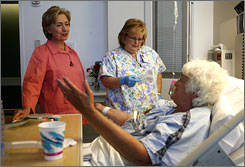 Presidential candidate Hillary Clinton makes the rounds with St. Rose Dominican Hospital nurse Michelle Estrada as they tend to patient Kristine Arone.