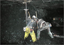Unidentified miners clear the mine passageway of the Crandall Canyon Mine in an effort to reach six trapped miners inside the mine.