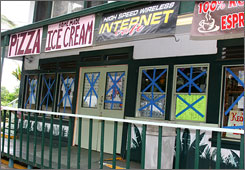 Blue tape covers the windows of businesses closed in Naalehu, Hawaii, on Tuesday in preparation for Hurricane Flossie.