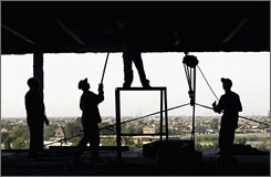 "Constructions workers perform their duties at a gutted building in Baghdad. Inspector general Stuart Bowen dubbed Iraq contract fraud the ""second insurgency."""