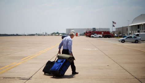 White House Deputy Chief of Staff Karl Rove wheels his luggage away from Air Force One on Monday upon arrival at Texas State Technical College Airport in Waco, Texas.