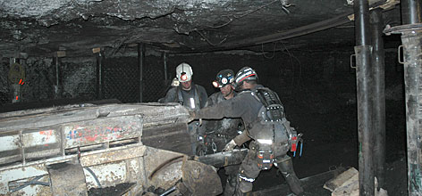 Three workers clear a mine passageway of the Crandall Canyon Mine in an effort to reach the six trapped miners. Murray Energy Corp. owner Bob Murray maintains hope that the miners will be found alive.