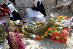 An injured woman lays on a path after receiving first aid Wednesday after the coordinated suicide blasts.