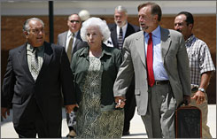 Defendants Salvador and Mabel Mangano walk with lawyer James Cobb, right, outside the courthouse Monday.