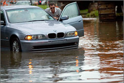 Robert Delano pushes his car after it stalled in high water after heavy rains drenched the area Thursday, Aug. 16, 2007, in Houston. Tropical Storm Erin's remnants soaked a rain-weary state Thursday, inundating intersections and killing at least five people.