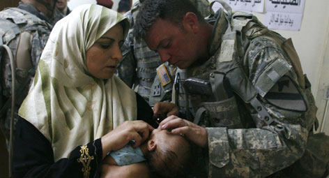 Staff Sgt. William Cyse checks on a small Iraqi girl during a medical clinic provided by the U.S. Army in a Baghdad neighborhood. Navy Cmdr. Steve Frost, who has supervised the construction of clinics in and around Baghdad, says he is concerned about growing medical staffing shortages around Iraq.
