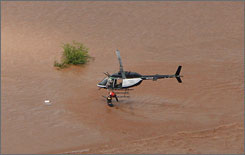 An Oklahoma Highway Police helicopter rescues a man whose pickup was washed off the roadway, in Kingfisher, Okla., Sunday.