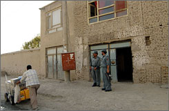 Two Afghan policeman stand next to the house where Meier was held by her kidnappers in Kabul.