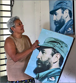 An employee decorates her workplace in Havana with pictures of Cuban President Fidel Castro on his 81st birthday, August 13th, 2007.