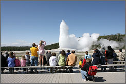 Visitors watch Old Faithful spray at Yellowstone National Park in May. A push is on to secure $26 million to replace the visitor center.