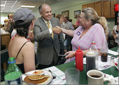 Former New York City mayor Rudy Giuliani shakes hands with Paula Weinberger during campaign stop Aug. 16 in Pelham, N.H.