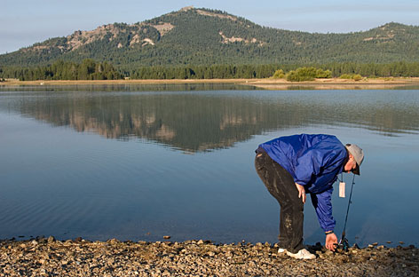 Bob Morris, 49, from Portola, Calif., reels in a bit of slack from the belly of his fishing line on the bank of Lake Davis, Saturday, Aug. 11. In order to eradicate the non-native northern pike, Lake Davis is to be poisoned for the second time in little more than a decade.