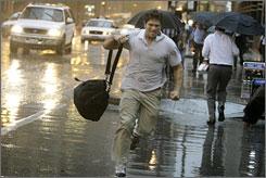 Pedestrians scramble through violent rain storms that hit downtown Chicago, Thursday.