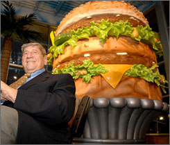 Jim Delligatti, inventor of the Big Mac, poses with the world's largest Big Mac statue (14 foot high and 12 foot wide) during the opening of the Big Mac Museum Restaurant in North Huntingdon, Pa.