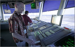 Could there be less work in their future? Air-traffic controllers Tom Sargent, left, and Dwayne Schuck issue commands at New York's JFK Airport.
