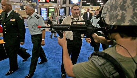 General George William Casey Jr., U.S. Army Chief of Staff, second from left, walks past a life-like mannequin wearing military garb and a weapon, one of many displays set up by defense contractors at the annual General Conference of the National Guard Association of the United States, in San Juan, Puerto Rico.