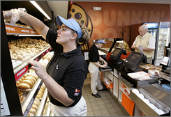 Frankie Morris, left, fills a costumer's order at a Dunkin' Donuts store, in Franklin, Tenn., in this Oct. 2006 file photo.