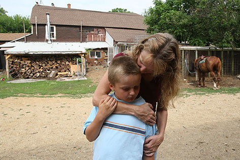 Kristan Gibbs, 40, gives her son Alex Gibbs, 9, a hug at Lake Village Homestead in Kalamazoo, Mich., as she gets ready to leave for work. Kristan's father, Roger Ulrich, founded Lake Village Homestead in 1971, and she spent much of her childhood there, later returning with her husband, Rod Gibb, to raise their two sons on a parcel of land adjacent to the main farm.