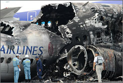 Investigators examine the burnt-out China Airlines Boeing 737 jet liner the day after it exploded in Okinawa, Japan.