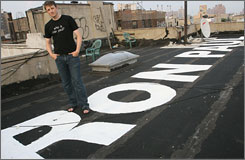 "Ron Paul supporter Avery Knapp poses for a photograph beside part of a sign for presidential hopeful Paul on the rooftop of a building in the East Village neighborhood of New York on August 16, 2007. The entire sign reads ""Google Ron Paul."""