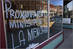 "A storefront window on Main Street indicates in Spanish that a new ""minisuper"" or small grocery store will open there to attract some of the growing Hispanic population in Marshalltown, Iowa."