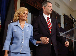 Former New Jersey Gov. James E. McGreevey, right, holds his wife Dina Matos McGreevey's hand, before announcing his resignation in 2004.