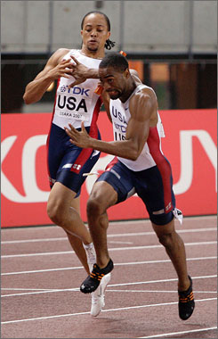 United States' Wallace Spearmon, left, hands over the baton to Tyson Gay as the US' Men's 4x100m Relay win the gold medal during the World Athletics Championships Saturday, in Osaka, Japan.