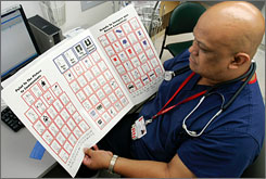 Robert Cagadoc, a registered nurse at University Hospital in Newark, N.J., looks over an emergency room picture board Friday, Aug. 31. Picture boards have drawings and symbols as well as English and Spanish words to help patients who don't speak English describe their ailments to emergency medical staff.