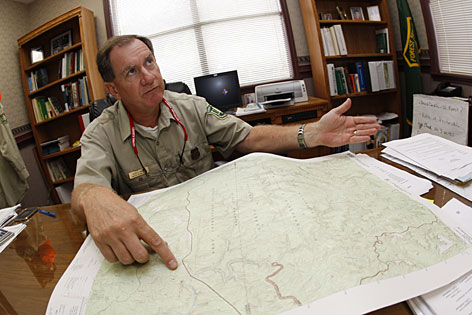 Large swath of land: District ranger Glen Gaines looks over a map of Bankhead National Forest from his office in Double Springs, Ala. More hikers are getting lost each year, according to park officials, rescue associations and sheriff's offices who say they have to coordinate more rescue missions than before.