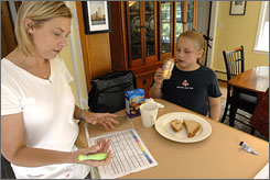 Teresa Osborne, left, notes a lunchtime caloric intake for her daughter Reagan Williams, right, in their Westborough, Mass., home. Reagan, 9, was diagnosed May 31 with Type 1 diabetes.