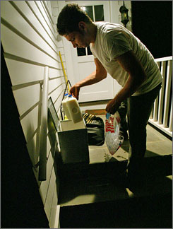 Ashraf Alfqelh delivers half-gallons of milk to a home in Chatham Township, N.J. Beginning at midnight each shift, Alfqelh makes deliveries in a halfdozen towns for four hours for McDana Dairy.