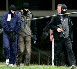 A terror suspect, left, is escorted to a helicopter by German police after questioning by prosecutors at a federal court in Karlsruhe, Germany.