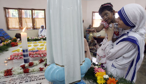 A nun of the Missionaries of Charity helps an orphan child to see the tomb of Mother Teresa during a commemoration of her 10th death anniversary in Calcutta, Wednesday. Mother Teresa, dedicated to working among the sick and destitute of this sprawling city, died days after celebrating her 87th birthday in 1997.