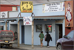 People walk past the bars on Front Street in Nome, Alaska.